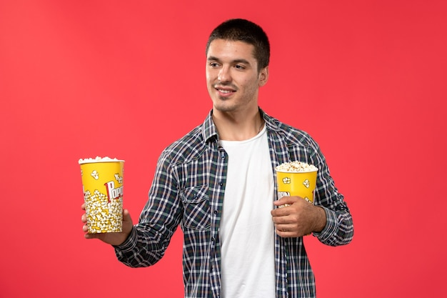 Front view young male holding popcorn packages on the light-red wall cinema movie theater film male