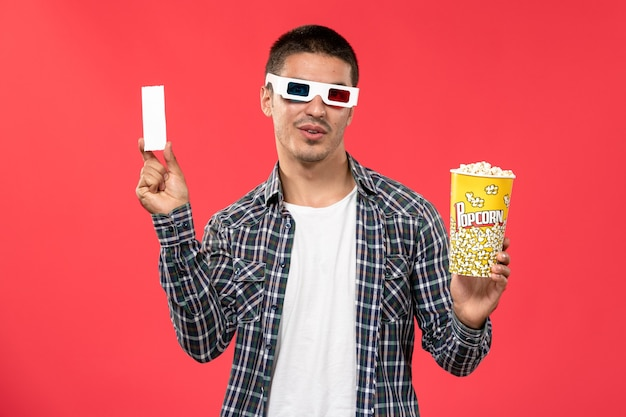 Front view young male holding popcorn and ticket in -d sunglasses on red wall movie theater cinema film