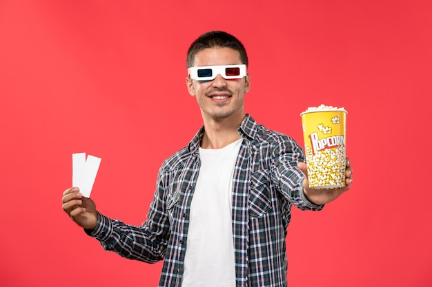 Front view young male holding popcorn and ticket in -d sunglasses on the red wall movie theater cinema film