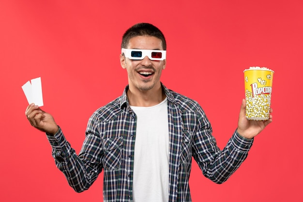 Front view young male holding popcorn and tickets in -d sunglasses on light red wall male movie theater cinema film
