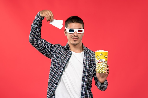 Front view young male holding popcorn tickets in -d sunglasses on light red wall male movie theater cinema film