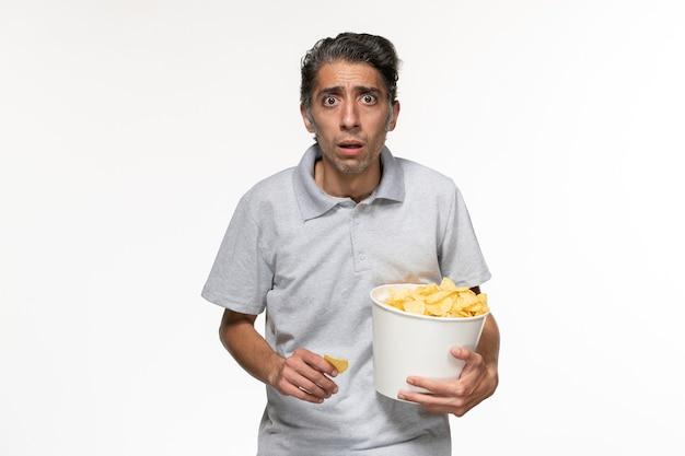Вид спереди молодой мужчина держит картофельные чипсы и смотрит фильм на белой поверхности