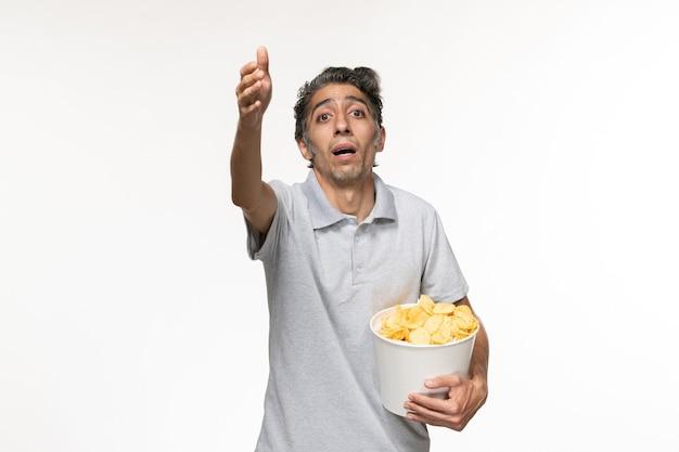 Giovane maschio di vista frontale che tiene le patatine fritte sulla superficie bianca