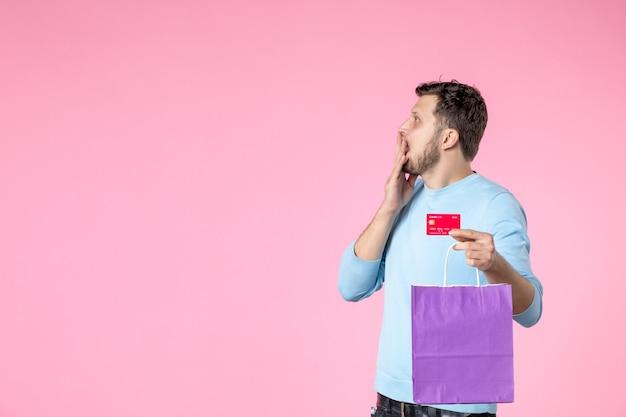 ピンクの背景に紫色のパッケージと銀行カードでプレゼントを保持している正面図若い男性女性の官能的な楽しい平等女性の日3月結婚日公園の恋人