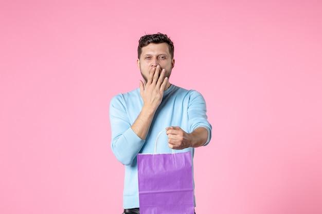 正面図ピンクの背景に紫色のパッケージでプレゼントを保持している若い男性官能的な平等女性の日行進愛フェミニンな日付結婚の楽しみ