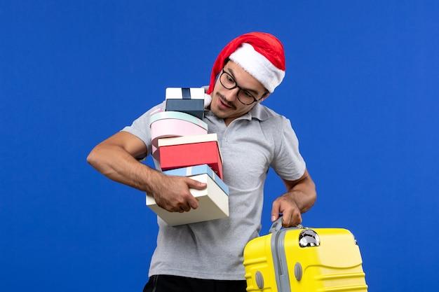 Вид спереди молодого мужчины, держащего подарки и сумку на синем фоне, летящие каникулы самолетов