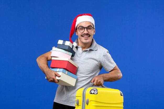 Vista frontale giovane maschio azienda presenta e borsa su sfondo blu voli aerei vacanza