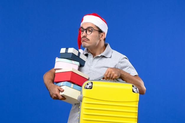 Vista frontale giovane maschio azienda presenta e borsa su sfondo blu aerei voli vacanza