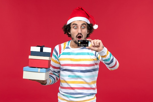 Front view young male holding presents and bank card on red wall new year money red male