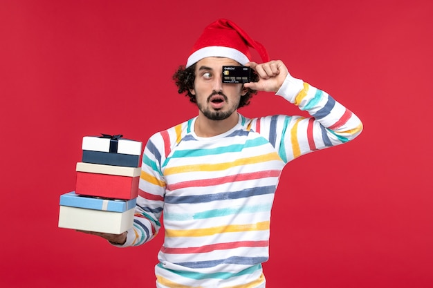 Front view young male holding presents and bank card on a red wall new year money red