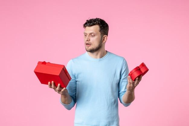 분홍색 배경 사랑 날짜 결혼 여성 관능적 인 여성의 날 3 월 수평 평등에 빨간색 패키지에 선물을 들고 전면보기 젊은 남성 프리미엄 사진