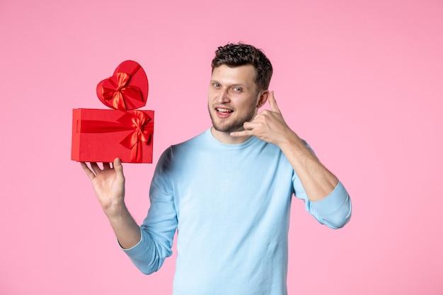 분홍색 배경 사랑 날짜 결혼 여성 관능적 인 여성의 날 3 월 가로에 빨간색 패키지에 선물을 들고 전면보기 젊은 남성
