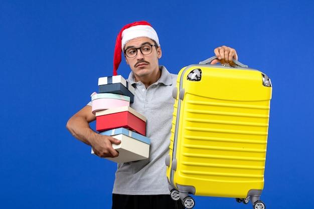 Вид спереди молодой мужчина, держащий подарки с сумкой на синем фоне, самолет, полет, отдых