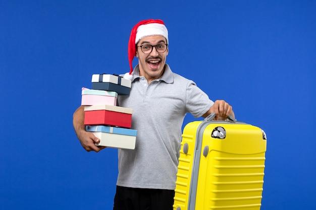 Вид спереди молодой мужчина, держащий подарки с сумкой на синем фоне, самолет, рейс, отдых
