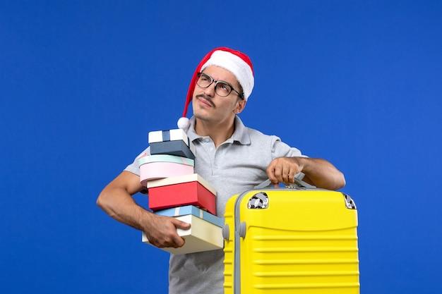 Вид спереди молодого мужчины, держащего подарки с сумкой на синем фоне, летние каникулы самолетов