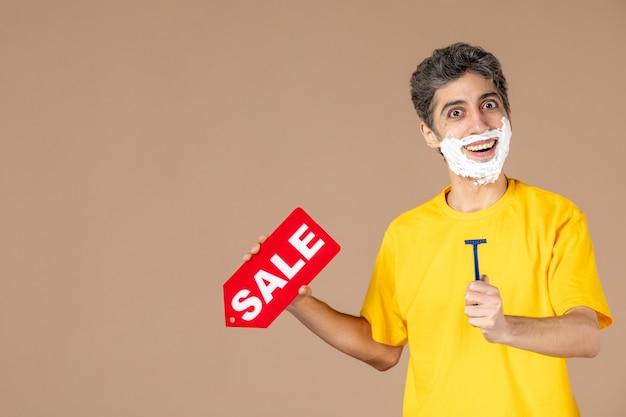 Vista frontale giovane maschio azienda rasoio e targhetta vendita rosso su sfondo rosa