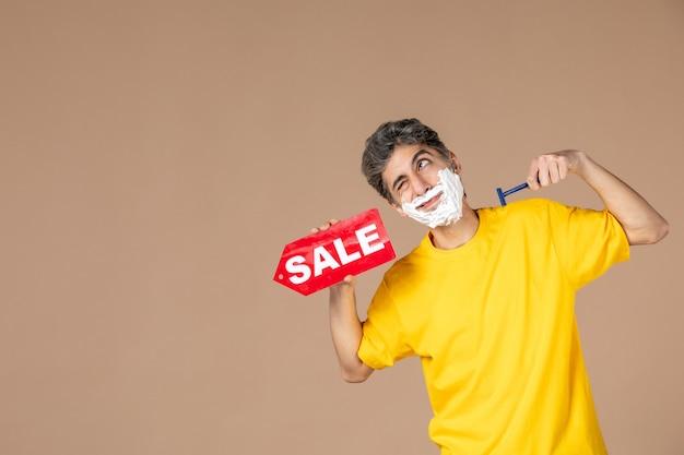 Vista frontale giovane maschio azienda rasoio e targhetta di vendita su sfondo rosa