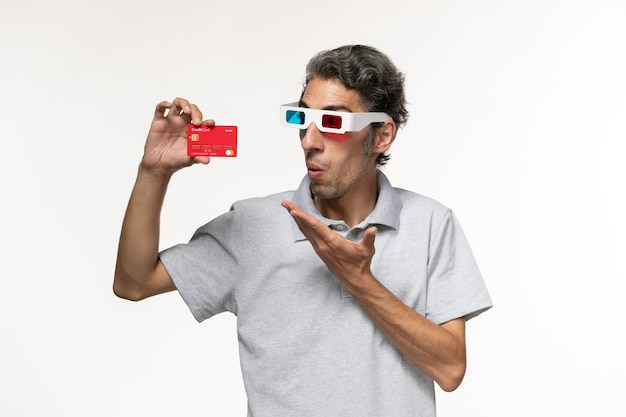 Front view young male holding red bank card in d sunglasses on a white surface