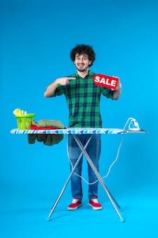 정면도 젊은 남성 파란색 배경에 빨간색 판매 쓰기를 들고 집 인간 세탁기 깨끗한 쇼핑 가사 세탁