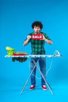 전면보기 젊은 남성 파란색 배경에 빨간색 판매 쓰기를 들고 집 인간 세탁기 깨끗한 쇼핑 집안일