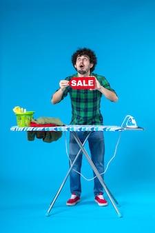 전면보기 젊은 남성 파란색 배경에 빨간색 판매 쓰기를 들고 집 인간 세탁기 깨끗한 쇼핑 세탁