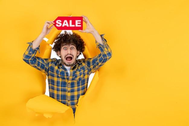 Вид спереди молодой мужчина держит красную распродажу на желтом разорванном фоне