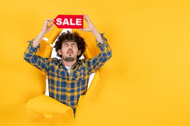 Front view young male holding red sale writing on the yellow ripped background