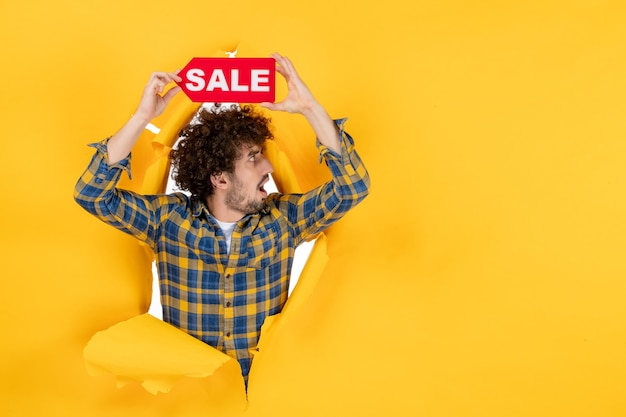 Front view young male holding red sale writing on yellow ripped background