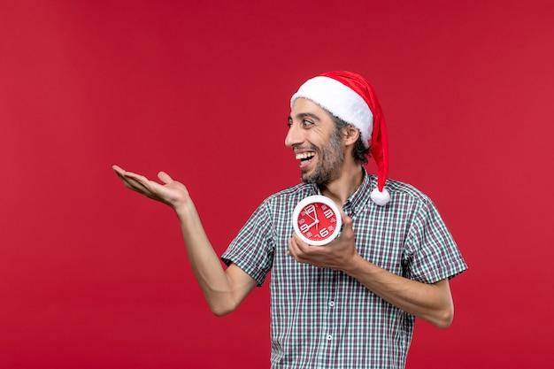 빨간색 바탕에 둥근 시계를 들고 전면보기 젊은 남성
