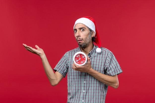 赤い机の上に丸い時計を保持している正面図若い男性