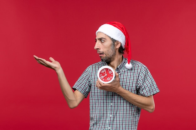 Front view young male holding round clocks on red floor emotion time red new year