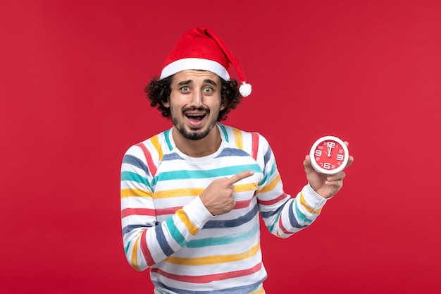 Front view young male holding round clocks on red wall time new year red holiday