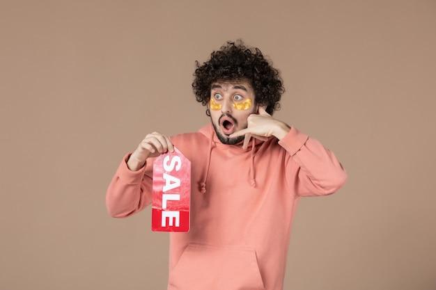 正面図茶色の背景に販売ネームプレートを保持している若い男性サロンスキンショッピングスキンケアセラピースパ顔マッサージ写真