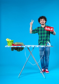Вид спереди молодой мужчина держит распродажу письмо на синем фоне дом человек стиральная машина цвет чистые покупки по дому