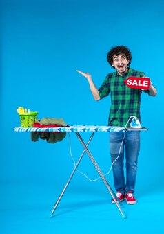Вид спереди молодой мужчина держит распродажу письмо на синем фоне дом человек стиральная машина цвета чистые покупки по дому