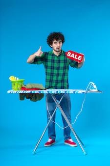 전면 보기 파란색 배경에 판매 쓰기를 들고 젊은 남성 집 세탁기 색상 깨끗한 쇼핑 가사