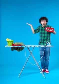 Вид спереди молодой мужчина держит распродажу писать на синем фоне человеческая стиральная машина цвет чистые покупки по дому