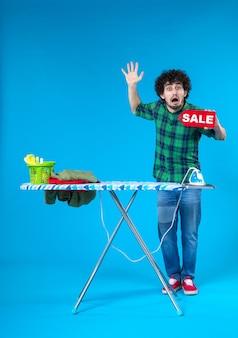 Вид спереди молодой мужчина держит распродажу писать на синем фоне человеческая стиральная машина цветной дом чистый шоппинг по дому