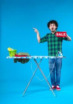 Вид спереди молодой мужчина держит распродажу писать на синем фоне человеческая стиральная машина цветной дом чистые покупки