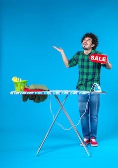 Вид спереди молодой мужчина держит распродажу писать на синем фоне человеческая стиральная машина цвета дома чистые покупки по дому