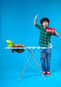전면보기 젊은 남성 파란색 배경에 판매 쓰기를 들고 인간의 세탁기 집안일 컬러 하우스 깨끗한