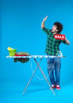 전면보기 젊은 남성 파란색 배경에 판매 쓰기를 들고 인간의 세탁기 집안일 컬러 하우스 쇼핑
