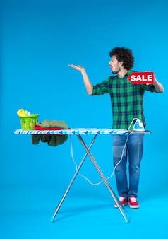 Вид спереди молодой мужчина держит распродажу писать на синем фоне человеческая стиральная машина работа по дому чистые покупки