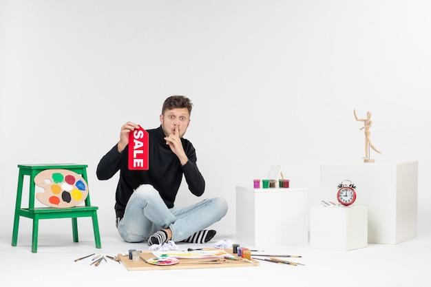 正面図若い男性が白い壁に販売を書いているアート画像カラージョブショッピングアーティストペイント