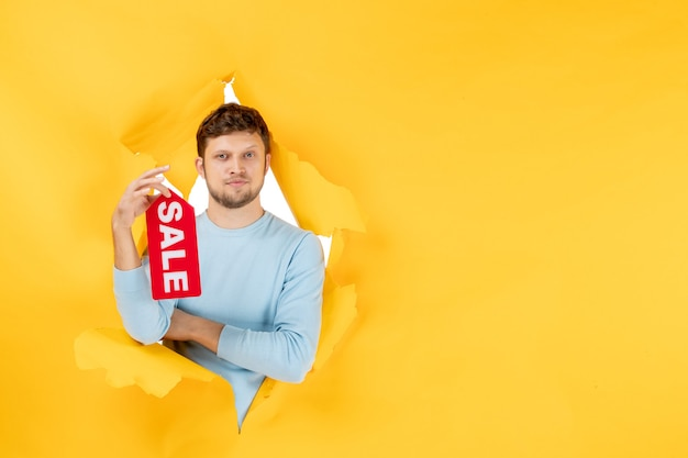 Front view young male holding sale writing on yellow ripped wall