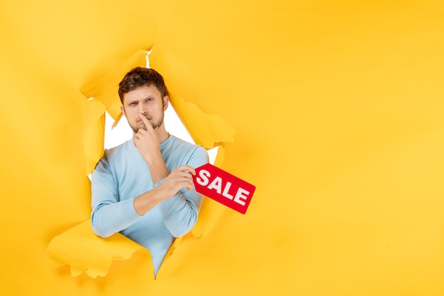 Front view young male holding sale writing on a yellow wall