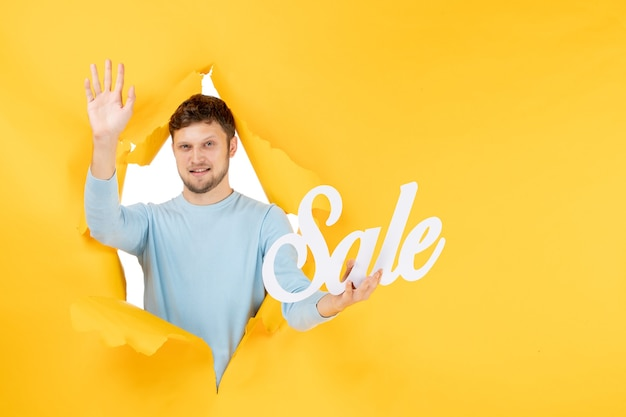 Front view young male holding sale writing on yellow wall