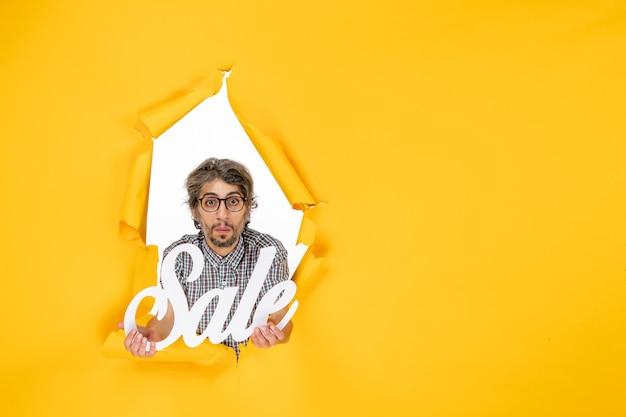 Vista frontale del giovane maschio che tiene la vendita scritta sul muro giallo
