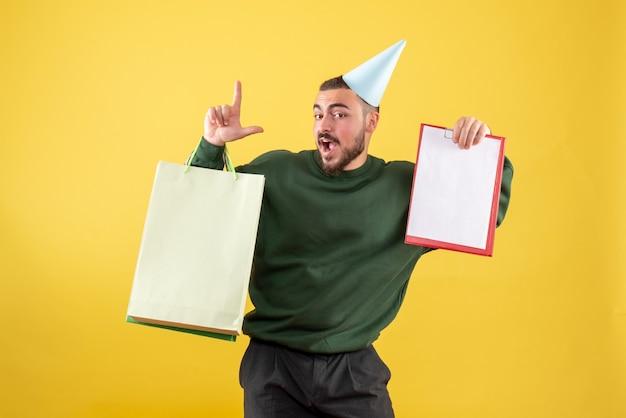 ショッピングパッケージと黄色の背景にメモを保持している若い男性の正面図