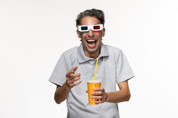 Giovane maschio di vista frontale che tiene soda in occhiali da sole d sul godimento di film a distanza della parete bianca solitario